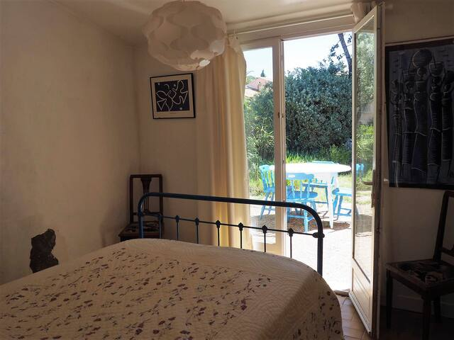 La chambre principale attenante à la salle de bains. Chambre donnant sur la terrasse arrière