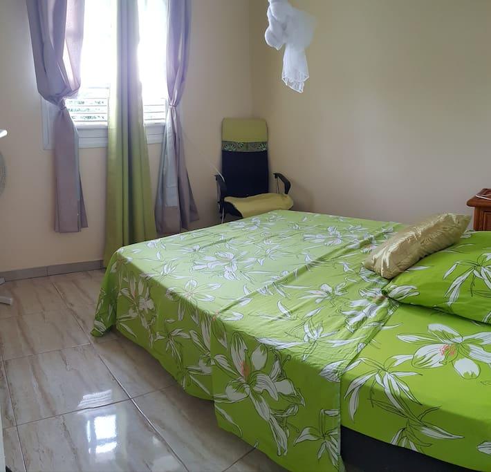 Chambre 1: Chambre équipée d'un lit double, d'un ventilateur, d'une moustiquaire, d'une table de nuit, une lampe de chevet, un fauteuil, un portant avec cintres, rideaux occultants. Surface: 9m2