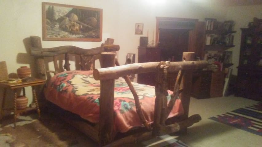 Master bedroom log bed . This is a huge bedroom . 30x15 feet with Jacuzzi tub, Large desk,  flatscreen tv , western magazine and book collection,  loads of movies, refrigerator,  and outside deck overlooking the Aspen  forest.