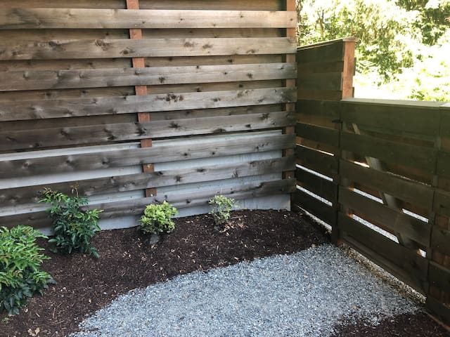 A gravel pathway enters an enclosed courtyard from the parking lot at 385 Erckson Ave NE. The key lock is on the fence.