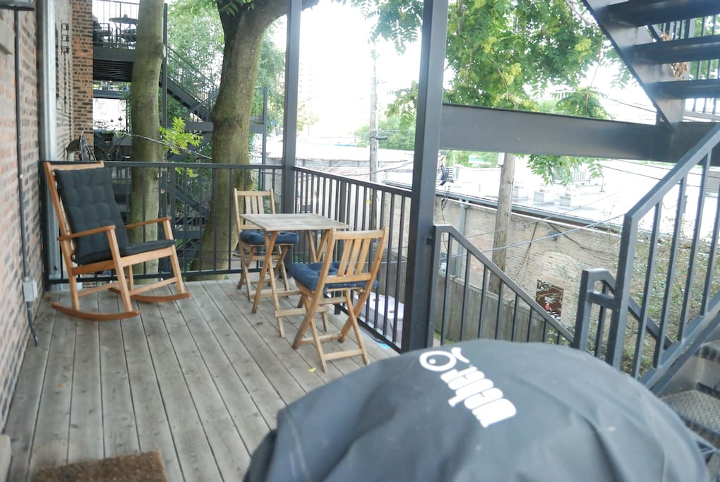 Deck with gas grill. The lights of Wrigley Field are visible in the distance when the Cubs are playing.