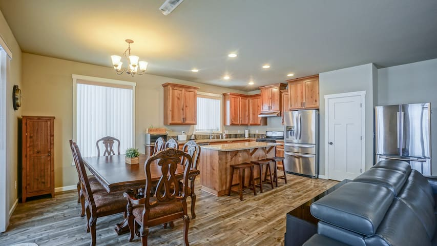 8 person dining table next to the gourmet kitchen with full size Refrigerator, gas ranger/over, and a dishwasher all in stainless steel.  The kitchen island has 3 bar stools for additional eating accommodation.