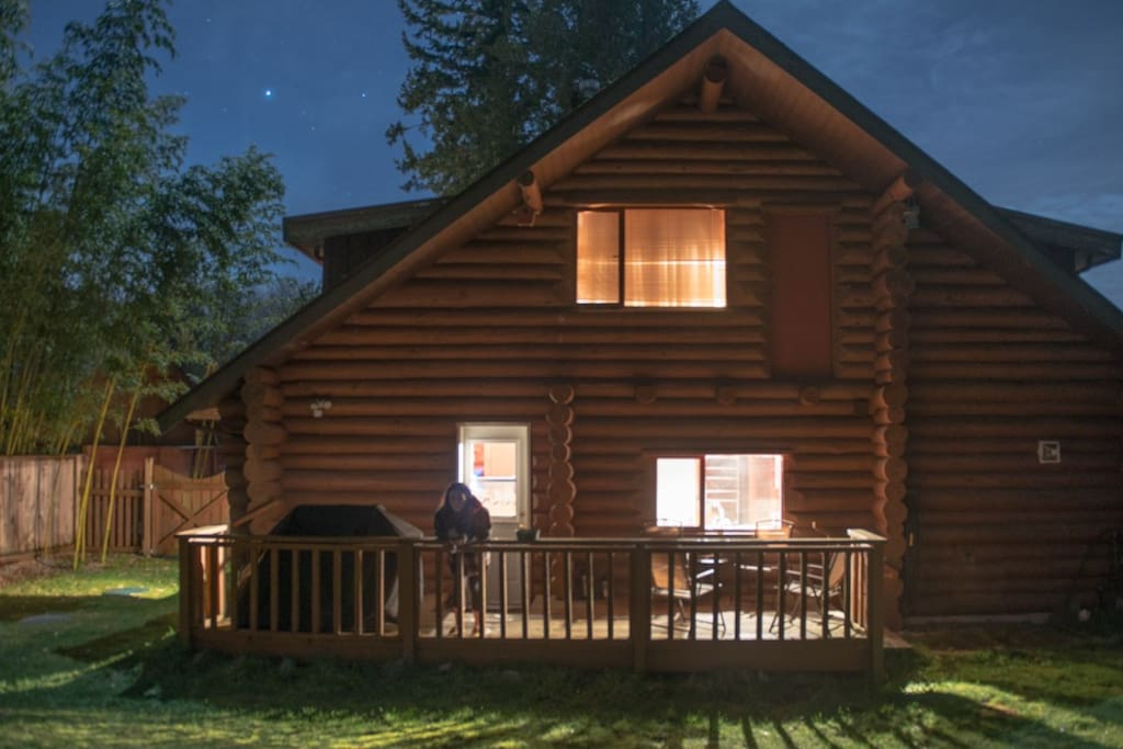 View of the back porch of the log cabin at night.