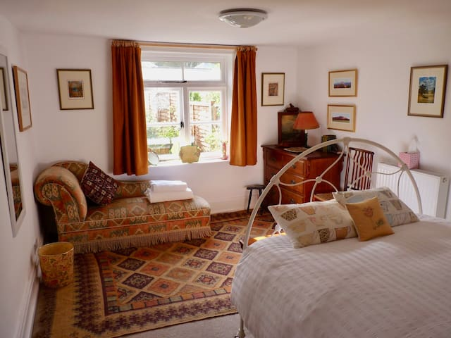 The Guest bedroom looks out over a pretty cottage garden and beyond to the hills of the Queen Elizabeth Country Park.