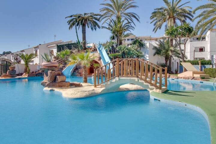 Community pool with water slides, beach proximity