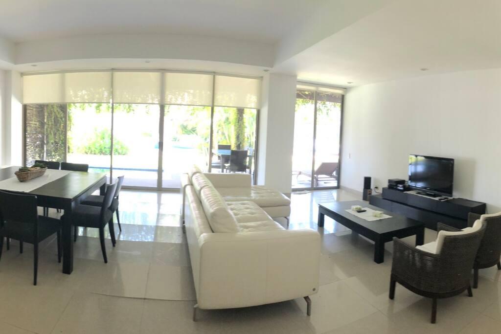 Barra de la cocina, sala y comedor, televisión.  Por  fuera terraza con jacuzzi, comedor y sala exterior