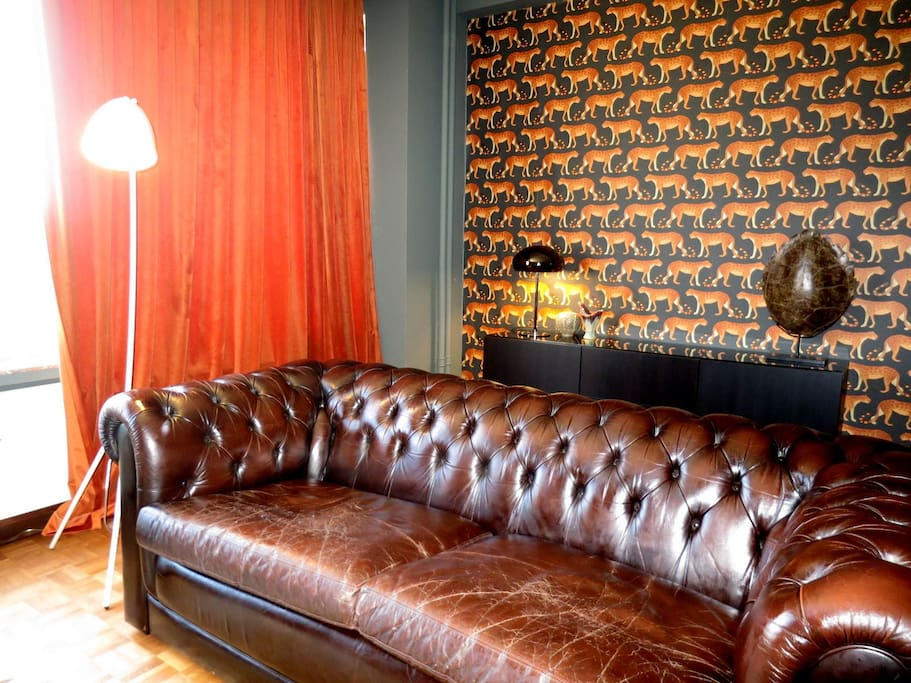 The large living room is richly decorated with a large Chesterfield and full length curtains.
