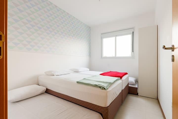 Segundo quarto com cama casal e duas camas auxiliares