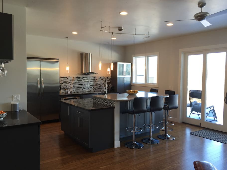 Open gourmet kitchen with bar fridge and plenty of bar seating