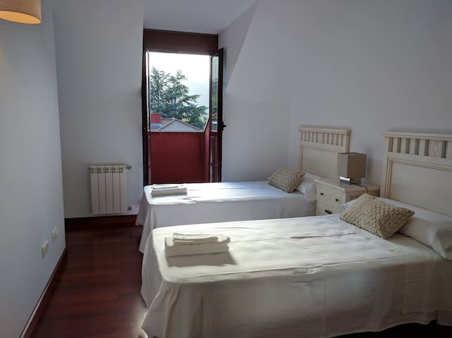Second bedroom with two beds, wardrobe and balcony