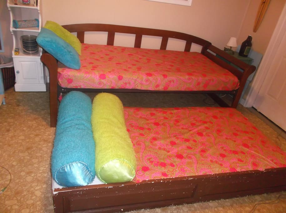 Trundle pulls out from under bed.  Does NOT pop up.  CANNOT be put together.   Slides back when not in use. DO NOT book if you want a double bed.