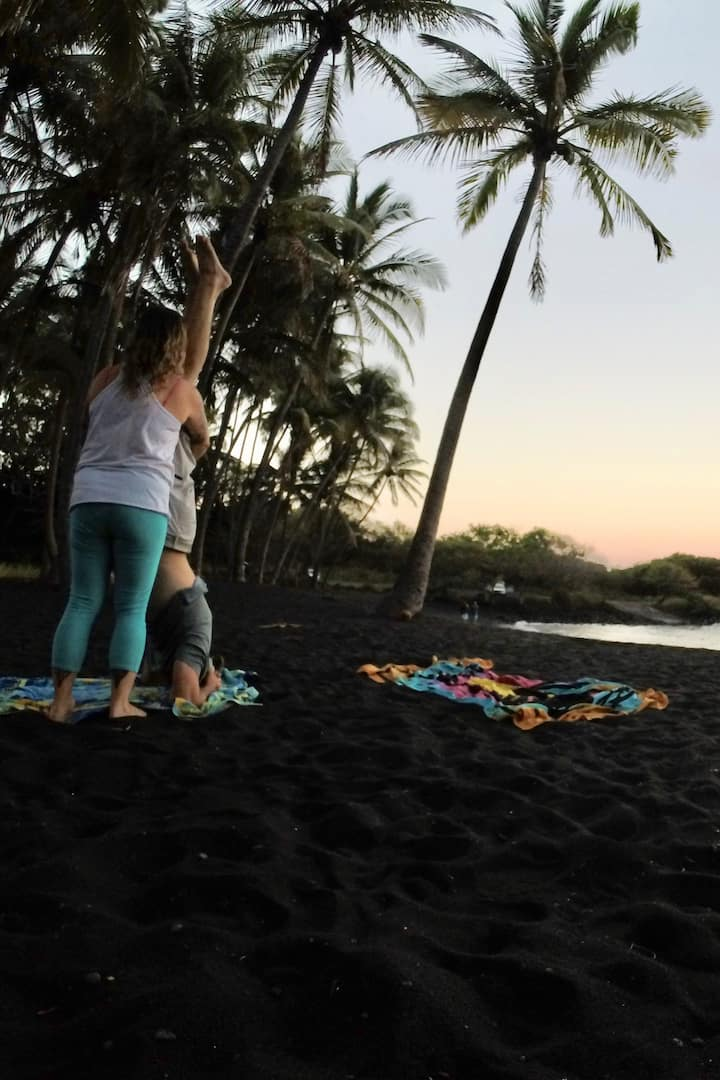Supported headstand in the black sand.