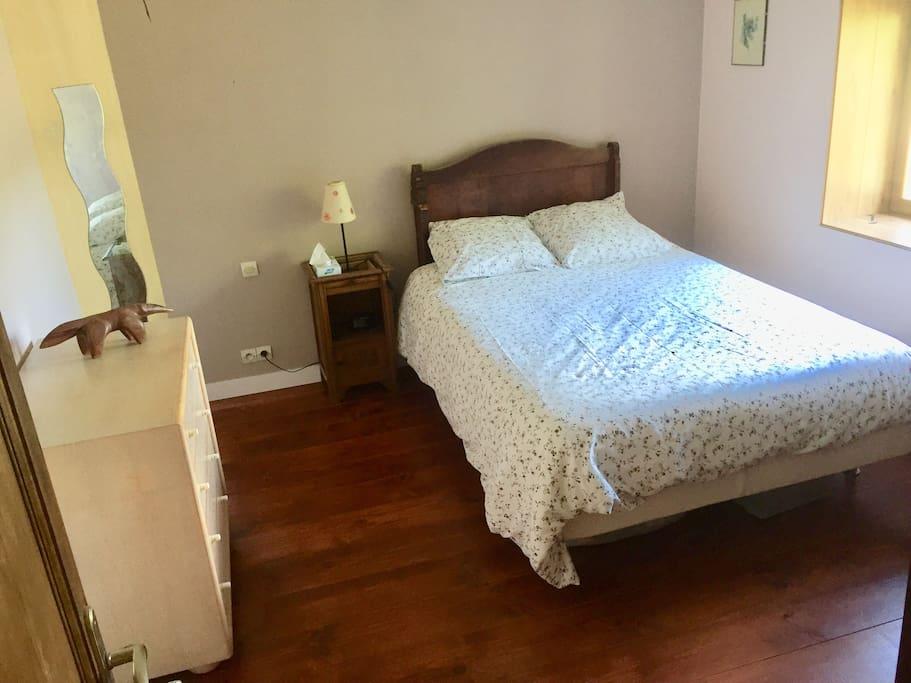 Chambre 2 avec un lit en 140 et un lit bébé en bois.