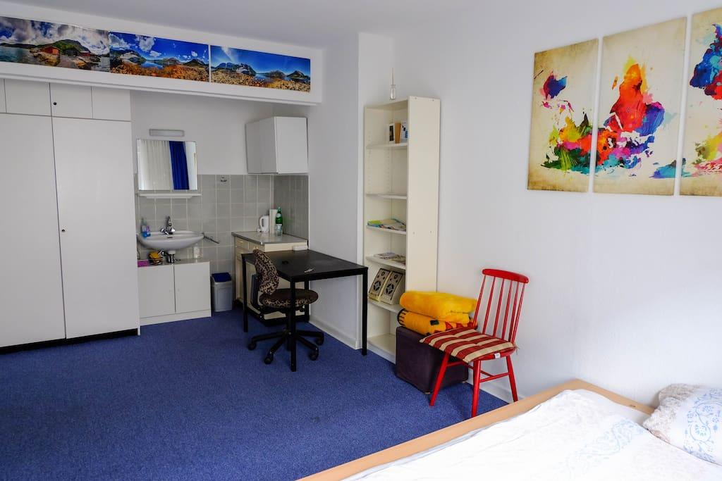 In dem großen, hellen Zimmer findest du alles, was du brauchst: Eine Kochnische, ein Waschbecken mit Spiegel, einen Ess-/Arbeitsplatz, Schränke und sogar Boxen
