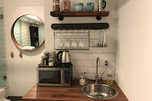 Kitchenette with refrigerator, microwave, kettle, coffee, a selection of tea, cereal, oatmeal, cookies, milk and half-n-half are all provided.  French press coffee maker.  Plates, mugs, glasses, bowls, silverware and knives.