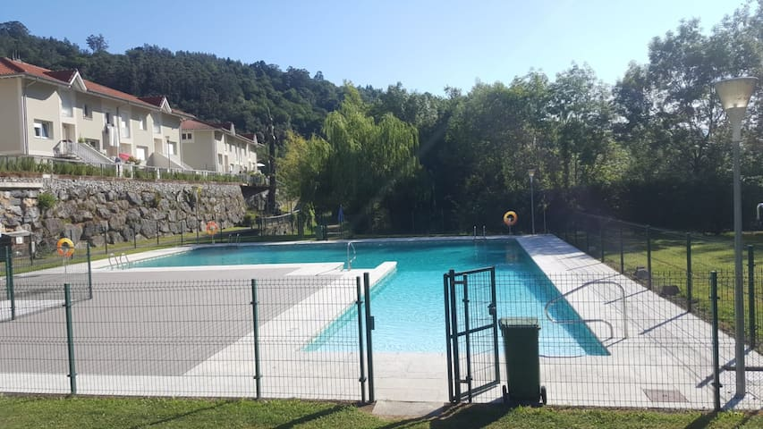 Chalet sobre piscina con vistas a montaña y río.