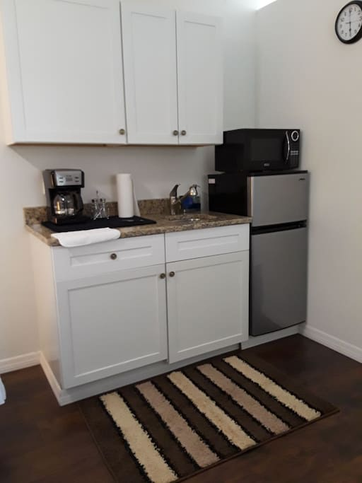 Kitchenette with basic items including a coffee maker, microwave, toaster, and basic items like coffee, sugar, water, tea, sugar, and more.