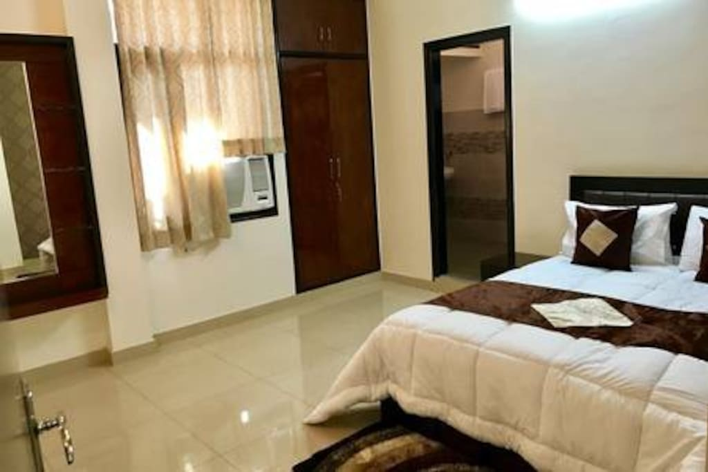 Designer bed with premium linen and attached bathrooms plus  Flat screen TV with Tata Sky HD showing international channels.