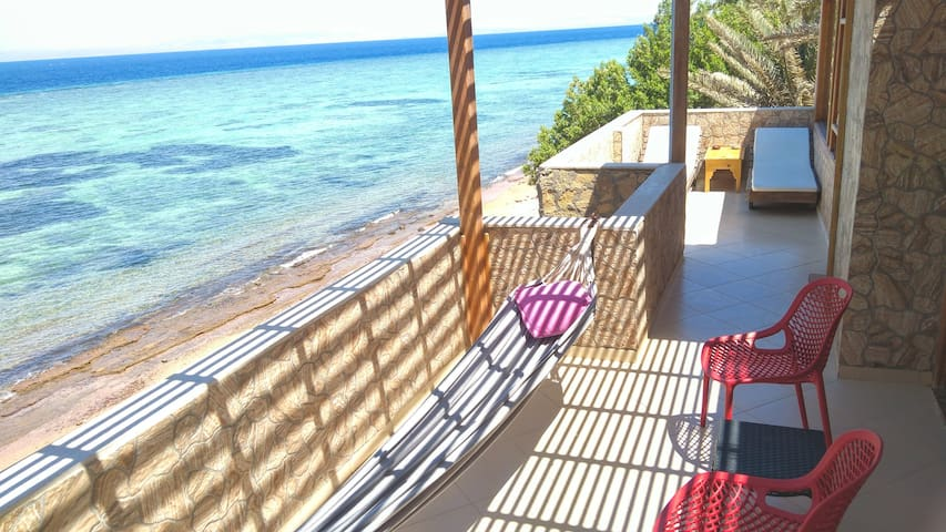 Terrace with hammock, sun beds, and sitting area.