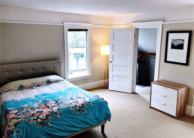 Queen bed and walk-in closet with refrigerator