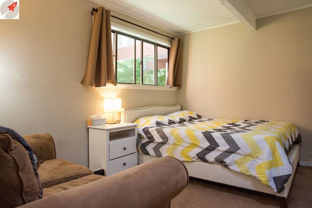 This room is sunny with large window and small skylight, equipped with queen bed, couch, and bedside table