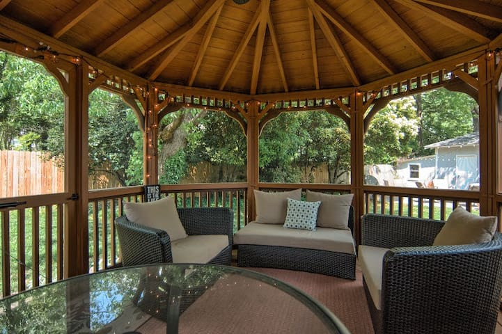 Screened in gazebo with comfy seating, a table for having dinner or breakfast, ceiling fan and lighting.