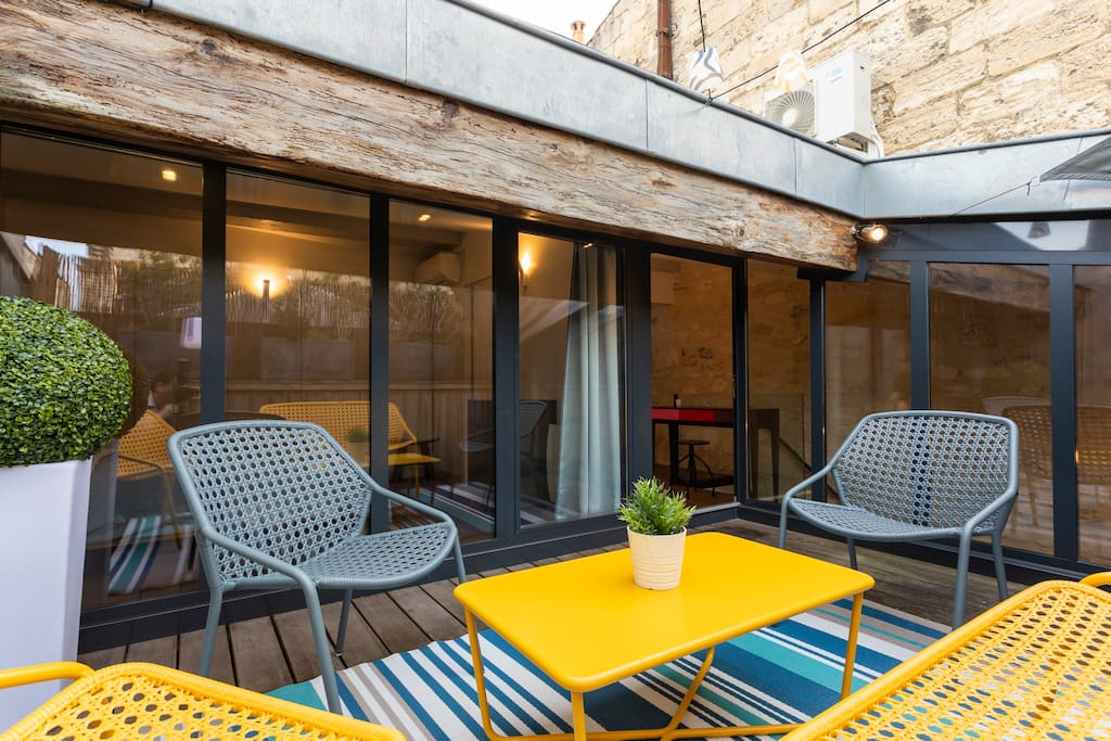 Cute patio area for your aperitifs! We added comfy high-quality FERMOB garden furniture and lighting. Photo taken in November.