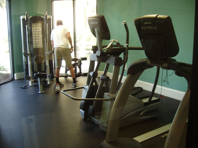 Fitness room with weight machine, eliptical and treadmill. TV to view while you're working out.