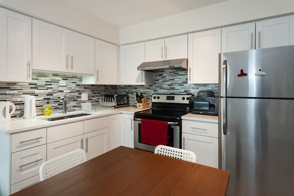 New and fully equipped kitchen with stainless steel appliances, quartz counter top, and tiled back splash.