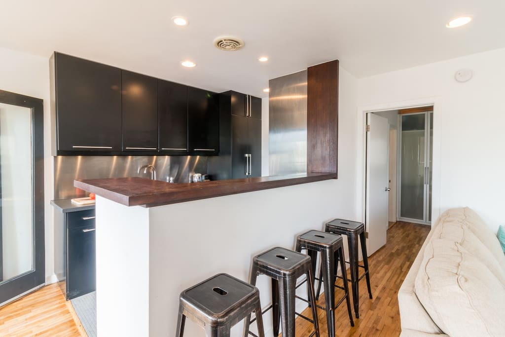 Designer, chef's kitchen lined with stained copper bar stools, stainless steel fixtures and granite countertops