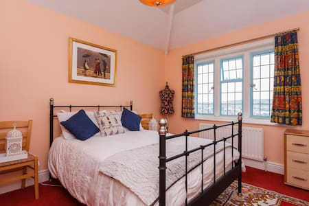 Our double room is warm, nicely decorated with a chest of drawers and wardrobe, wall mirror, ceiling light and two bedside lamps in centrally-heated, large, detached house overlooking Swanage bay with wonderful views of the bay and the Purbeck Hills.