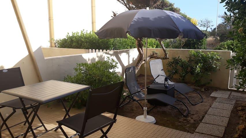 Terrasse avec table et chaises et jardinet