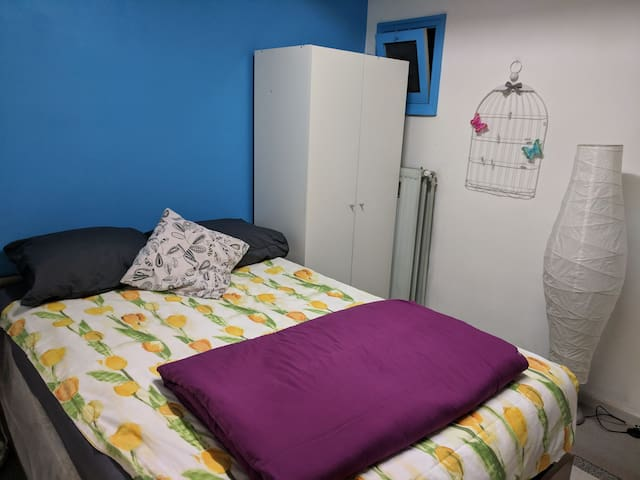 The room is equipped with cupboard to store clothes. Also note the small window. That is the one and only window in the room.