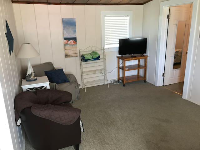 Living room view from front door; bedroom door on the right.