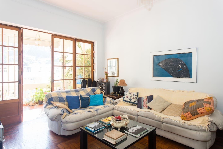 Grande salão com 2 sofás e mesa. Vista para a varanda.