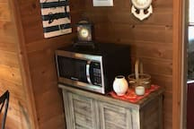 Microwave & storage cabinet with needed new disease, glassware, bowls  & other cooking supplies.