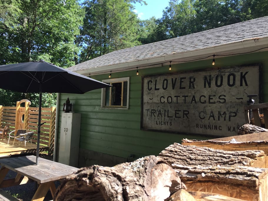 The outdoor area includes a picnic table with umbrella, propane grill, bistro lights, tall trees and the vintage sign - likely from the 1940s - that inspired the name... The Clover Nook.