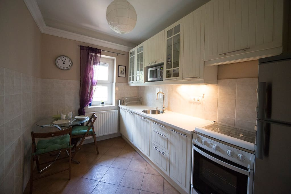 The spacious and comfortable kitchen with a dining table, a microwave oven, an oven, a fridge, a water heater, teamaker, coffee machine