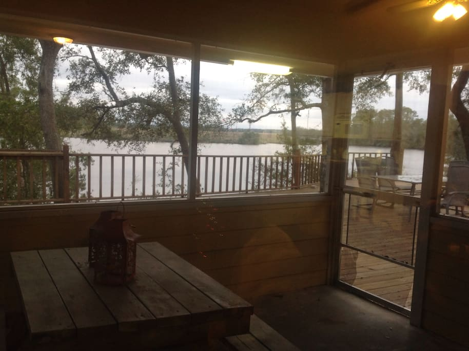 Covered porch with picnic table and elliptical. View from living room.