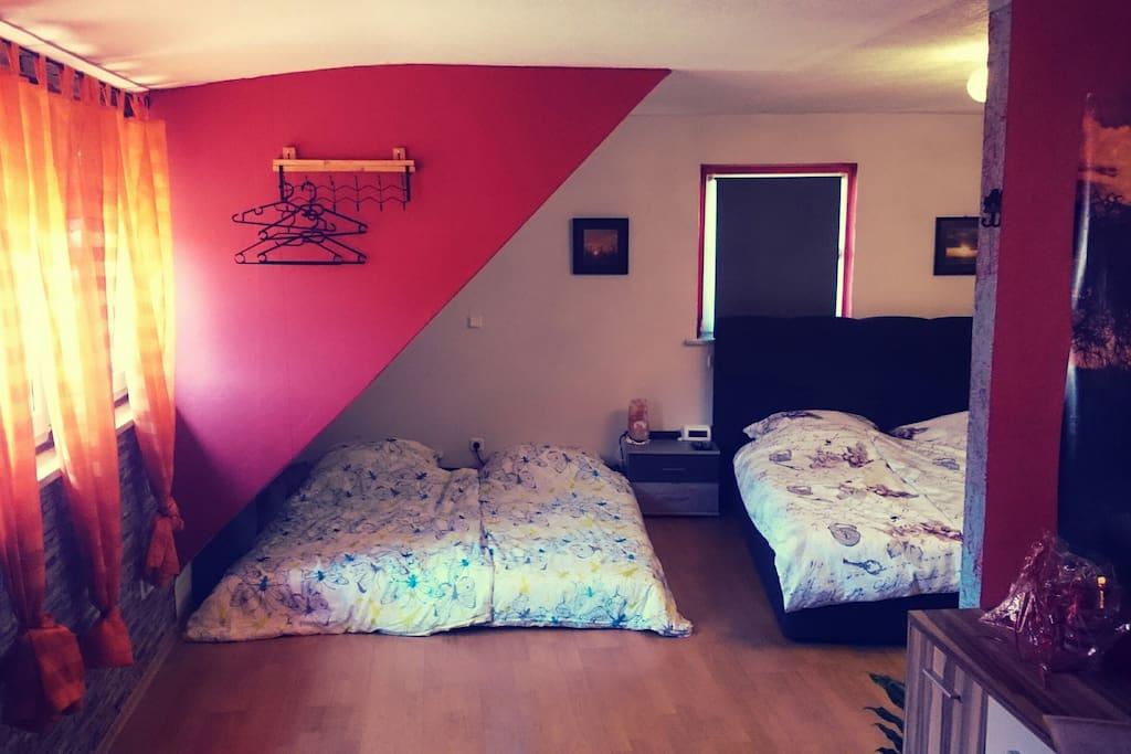 Großes Zimmer 2 ab 2 Personen, auch für Familien mit Kindern oder Gruppen gemeinsam nutzbar. Doppelbett 1,80m breit plus Matratzen nebendran möglich.