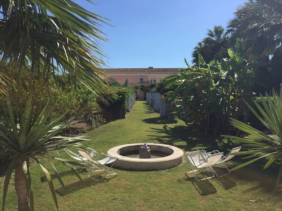 La villa bianca e rosa è al centro della proprietà di fronte ha il mare e dietro c'è il giardino che comprende anche la casa