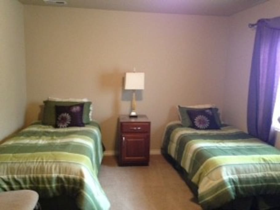 Second bedroom with two twin beds and a treadmill and a spacious closet.