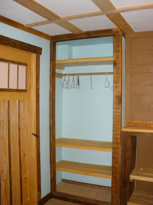 guest room with sliding door, closet and lots of shelving.