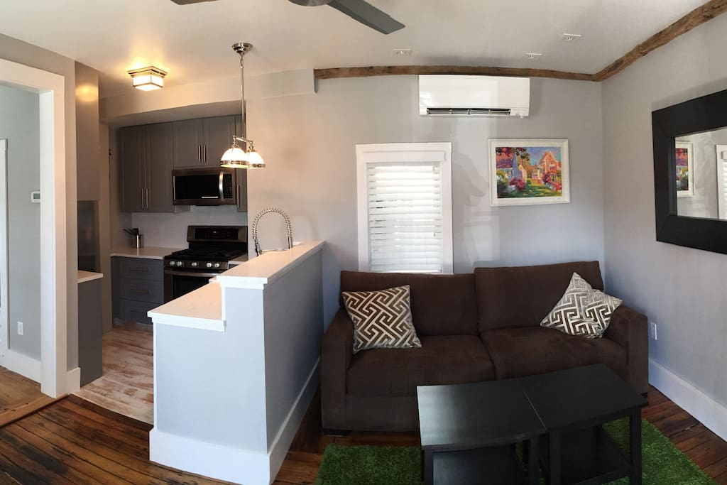 Panoramic shot of living room seating area, as well as the kitchen and entrance to bedroom (on the left).