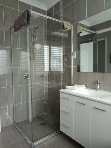 Semi-frameless shower and vanity in spacious  bathroom