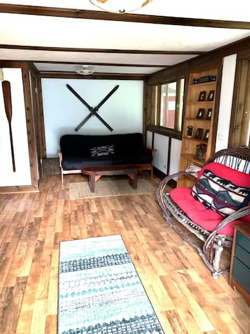 Sitting room features a rustic Adirondack space with board games, a  futon, and coffee table