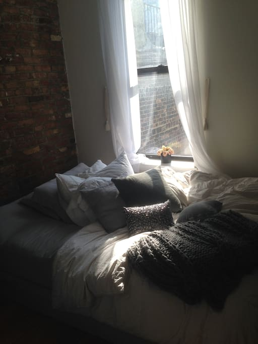 Other bedroom with exposed brick accent wall and west facing window