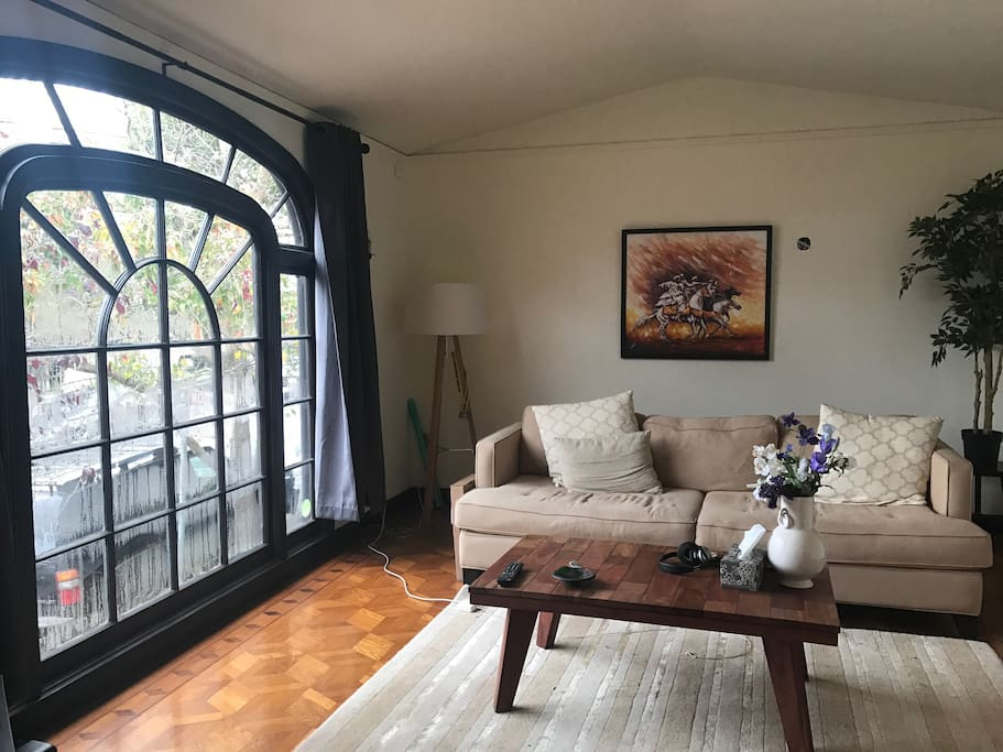 The living room has a spectacular arched window that lets lots of light in. (There is also a large TV behind the camera.)