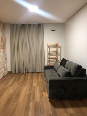 Sala de estar com confortavél sofá-cama e cortinas com BLACKOUT.