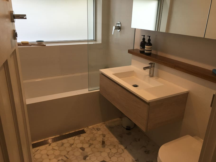Newly renovated master bathroom with bath and shower.
